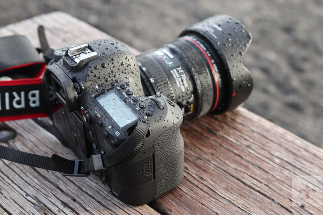 Higher angle and top-side of Canon EOS 6D Mark II, covered in droplets, facing away diagonal right on wooden table