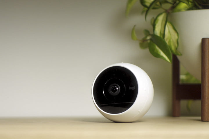 Security camera sitting on a wooden table next to a plant