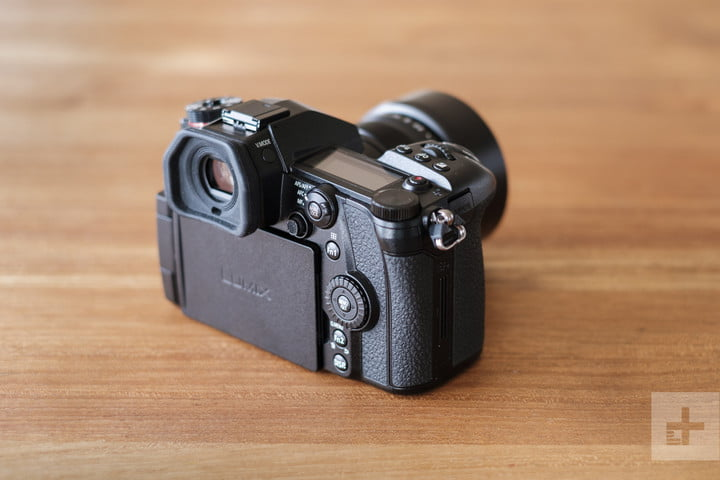 Panasonic Lumix G9 Review | Camera sitting on a table facing the top right corner of the frame, showing the back of the camera at an angle