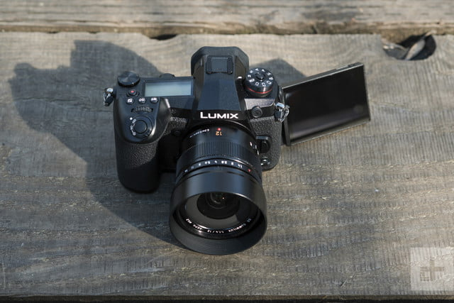 Panasonic Lumix G9 Review | Facing the camera, slightly elevated, showing the lens and front of the camera with the screen flipp
