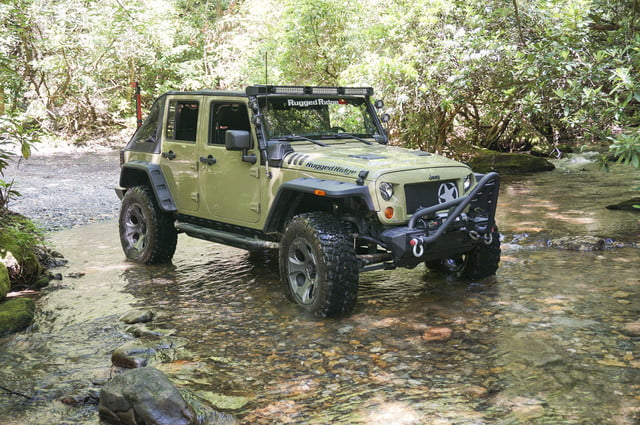 Green Jeep Wrangler Unlimited driving through a creek